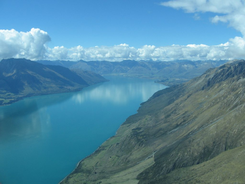 Fly over sparkling lakes nestled in the mountains on your way to Milford Sound